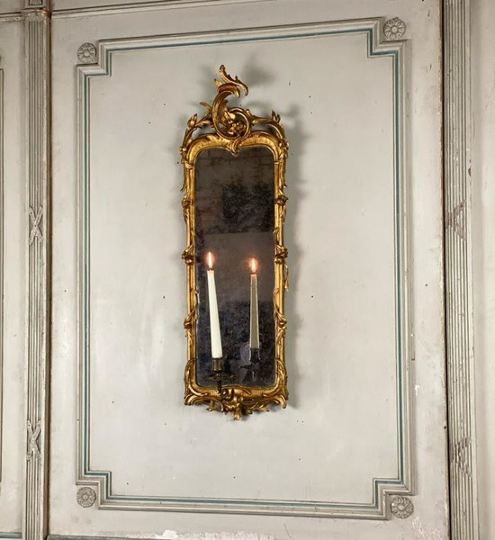 Carved gilded wooden mirror with an arm of light